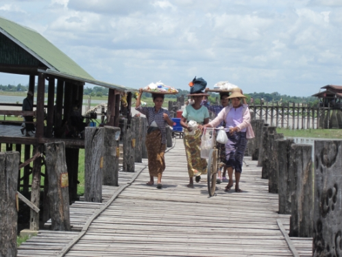 Locals use their heads to carry heavy goods across the bridge