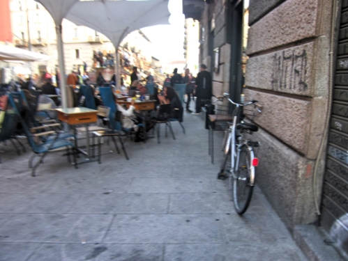 This bike owner is most likely enjoying happy hour, or aperitif, at this cafe