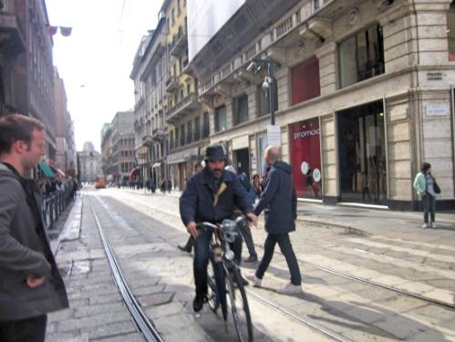 A stylish man biking near the Duomo